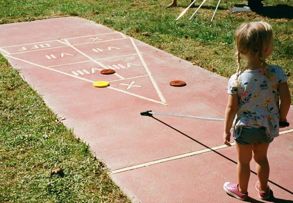 Child Plays Shuffleboard